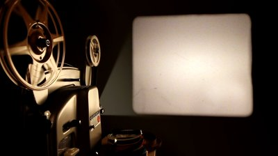 stock-footage-an-antique-mm-film-projector-projects-a-blank-movie-with-a-dust-and-hair-texture-lifted-from